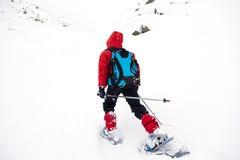 Jongen die in berg met sneeuwschoen lopen royalty-vrije stock foto's
