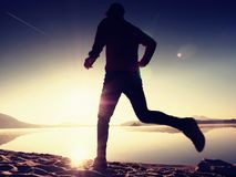 Jongen die bij het strand tijdens zonsopgang met bezinning lopen Het strand van de ochtendbaai met duidelijke hemel Stock Afbeelding