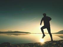 Jongen die bij het strand tijdens zonsopgang met bezinning lopen Het strand van de ochtendbaai met duidelijke hemel Stock Afbeeldingen
