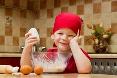 Jongen die bij keuken met bakselpastei helpt Stock Foto