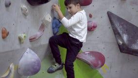 Jongen die binnenrotsmuur beklimmen stock footage