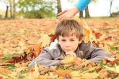 Jongen die in bladeren ligt Stock Foto's