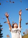 Jongen die bladeren in lucht werpt Stock Afbeeldingen