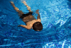 Jongen die in blauwe pool zwemt Stock Foto