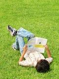 Jongen die buiten bestudeert Stock Foto's