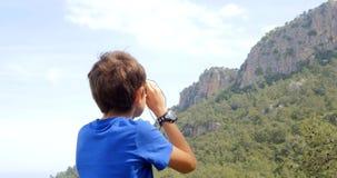 Jongen die de bergen bekijken stock video