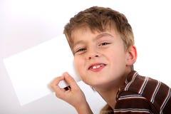 Jongen die de blanco pagina houdt Stock Afbeeldingen