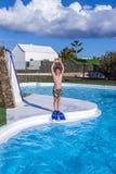 Jongen die in de blauwe pool springen Stock Foto's