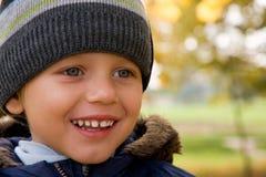 Jongen die in de herfstlandschap glimlacht Stock Foto