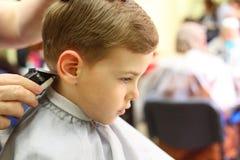 Jongen die in de machine van de kapper wordt gesneden Stock Afbeelding