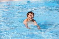 Jongen die in de pool zwemt Stock Afbeeldingen