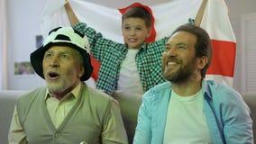 Jongen die de vlag van Engeland, familie golven die op de nationale gelijke van het voetbalteam thuis letten stock video