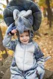 Jongen die dinosauruskostuum dragen Stock Afbeeldingen
