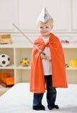 Jongen die document hoed, kaap draagt en een zwaard draagt Royalty-vrije Stock Afbeeldingen
