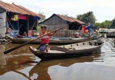 Jongen die door Boot in Tonle-Sapmeer reizen Stock Foto's