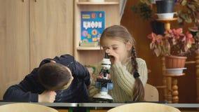 Jongen die door een microscoop kijken stock footage