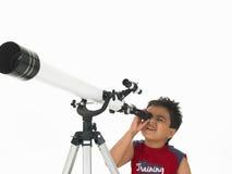 Jongen die door een telescoop kijkt stock fotografie