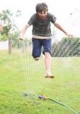 Jongen die door sproeier springen royalty-vrije stock fotografie