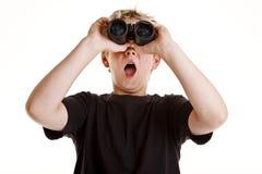 Jongen die door verrekijkers kijkt Stock Foto