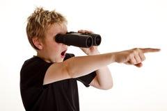 Jongen die door verrekijkers kijkt Stock Foto's