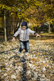 Jongen die in droge bladeren springen Stock Afbeelding