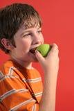 Jongen die een appelverticaal eet stock fotografie