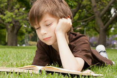 Jongen die een boek leest Stock Foto