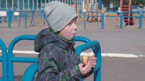 Jongen die een broodje op de speelplaats eten stock video