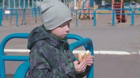 Jongen die een broodje op de speelplaats eten stock videobeelden