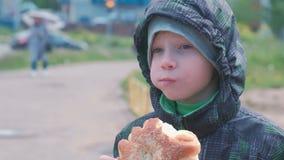 Jongen die een broodje op de straat eten stock videobeelden