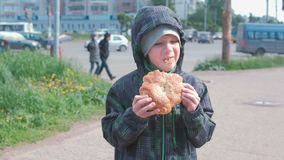 Jongen die een broodje op de straat eten stock footage