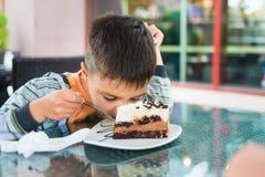 Jongen die een cake lage neiging over plaat in koffie eten stock foto's