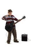 Jongen die een elektrische geïsoleerde gitaar speelt Royalty-vrije Stock Afbeeldingen