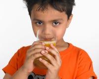 Jongen die een glas sap drinkt stock fotografie