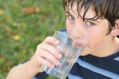Jongen die een glas water drinkt Stock Afbeelding