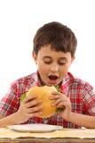 Jongen die een grote hamburger eet royalty-vrije stock afbeelding