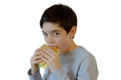 Jongen die een hamburger eet Stock Foto