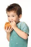 Jongen die een hamburger eten Stock Foto's