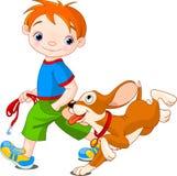 Jongen die een hond loopt Stock Afbeeldingen
