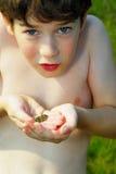 Jongen die een kikker houdt Stock Foto