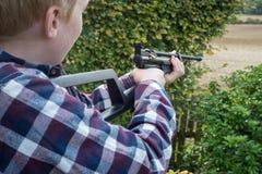 Jongen die een Luchtpistool streven Stock Afbeeldingen