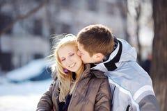 Jongen die een meisje in de winter kussen Royalty-vrije Stock Afbeelding