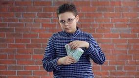 Jongen die een pakje van geldventilator houden stock video