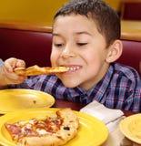 Jongen die een pizza eet stock afbeeldingen