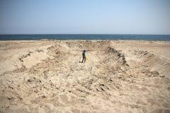 Jongen die een reusachtige kuilstuk speelgoed schop graven Stock Foto
