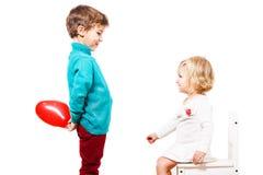 Jongen die een rode ballon geven aan het meisje Stock Afbeeldingen