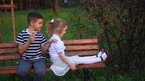 Jongen die een roomijs eten en op de bank zitten terwijl het meisje kijkt stock video