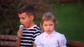 Jongen die een roomijs eten en op de bank zitten terwijl het meisje kijkt stock videobeelden