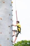 Jongen die een rotsmuur beklimmen Stock Foto