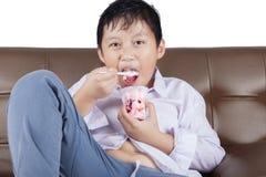 Jongen die een smakelijk roomijs op bank eten Royalty-vrije Stock Afbeelding